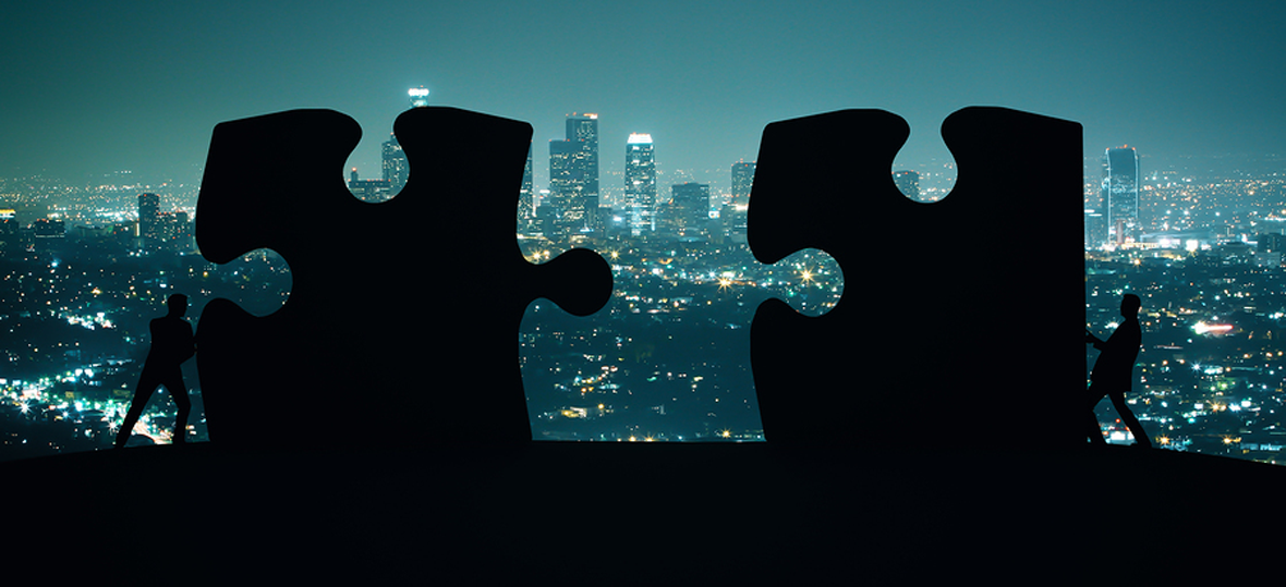 Businesspeople fitting puzzle pieces together with cityscape background