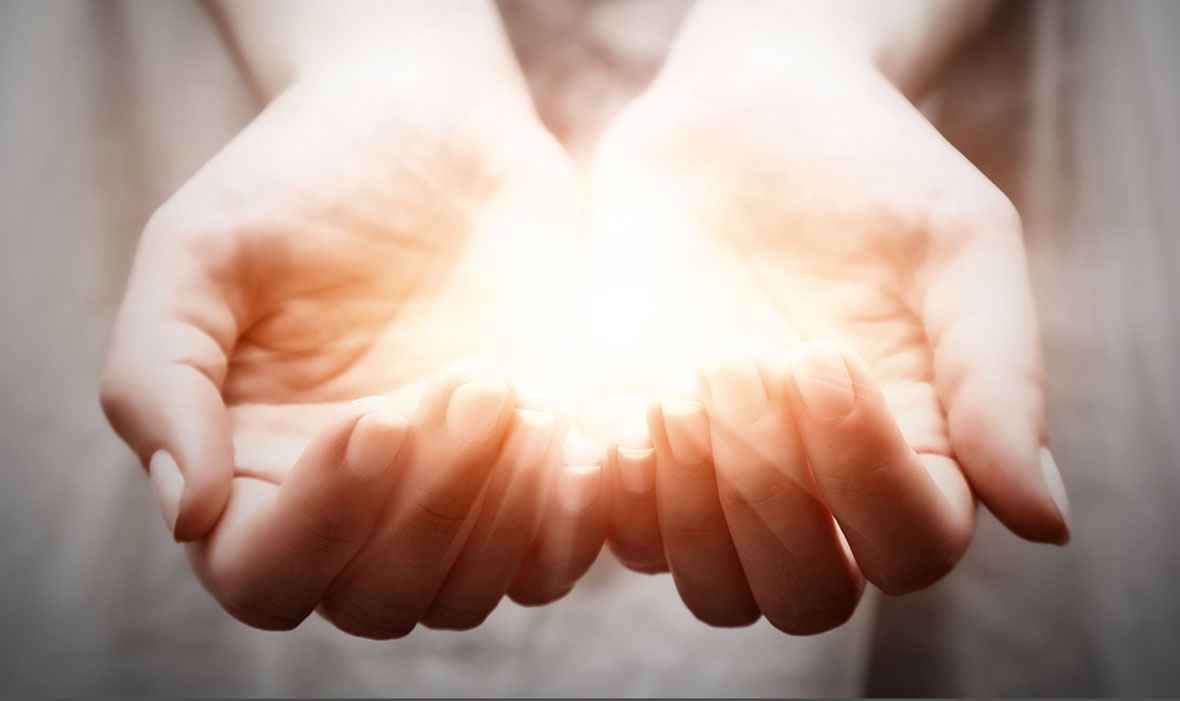 Two hands holding a warm light in a giving manner.