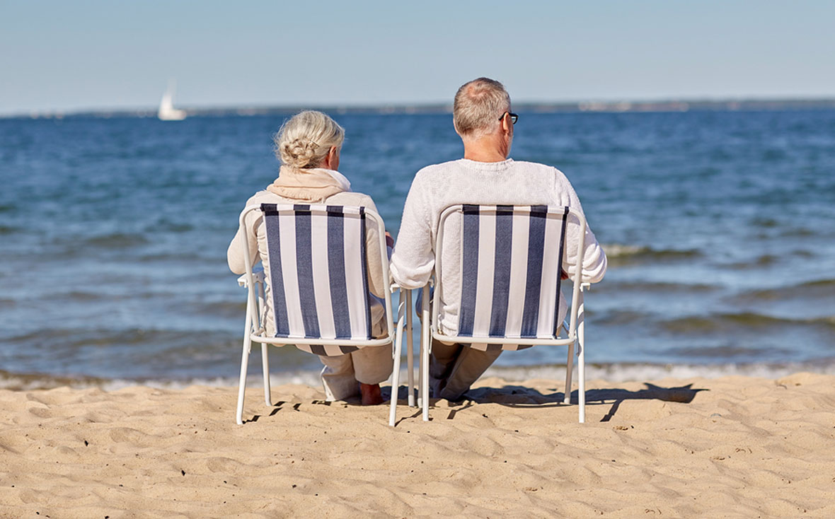 Senior couple sitting in deck chairs on the beach