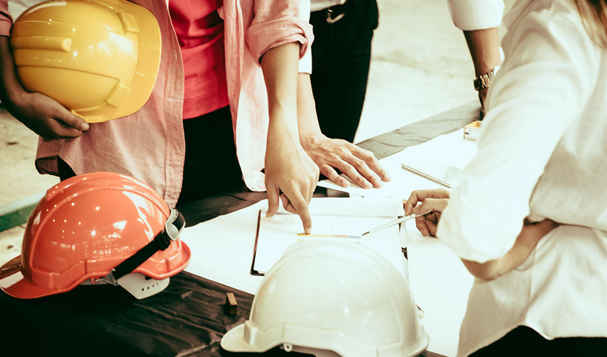Contractors standing over paperwork at construction site with hard hats.