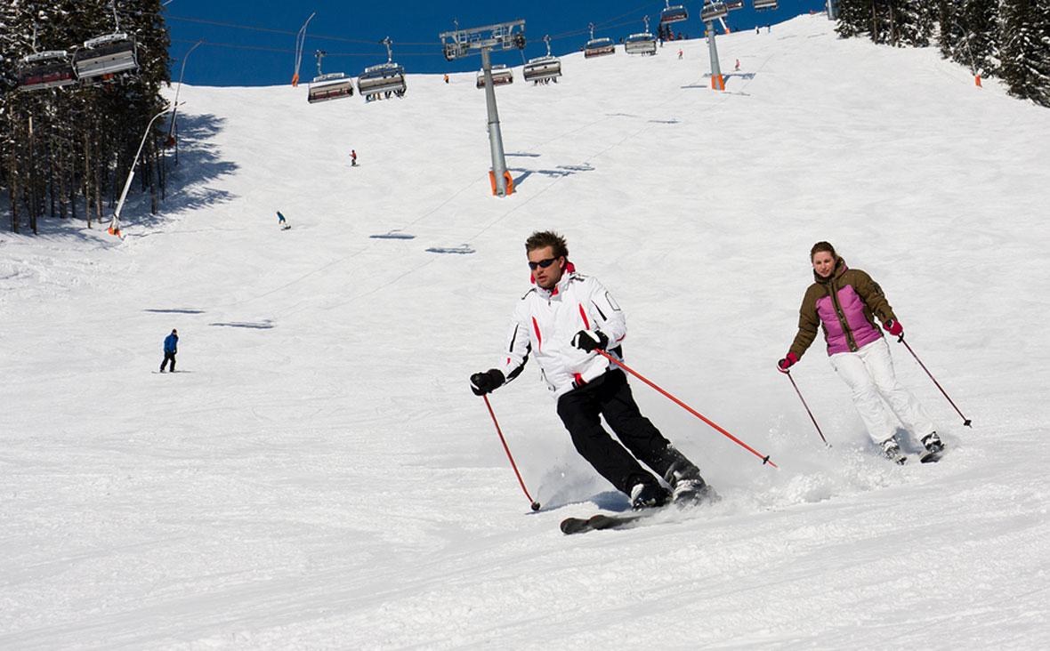 Man and woman downhill skiing